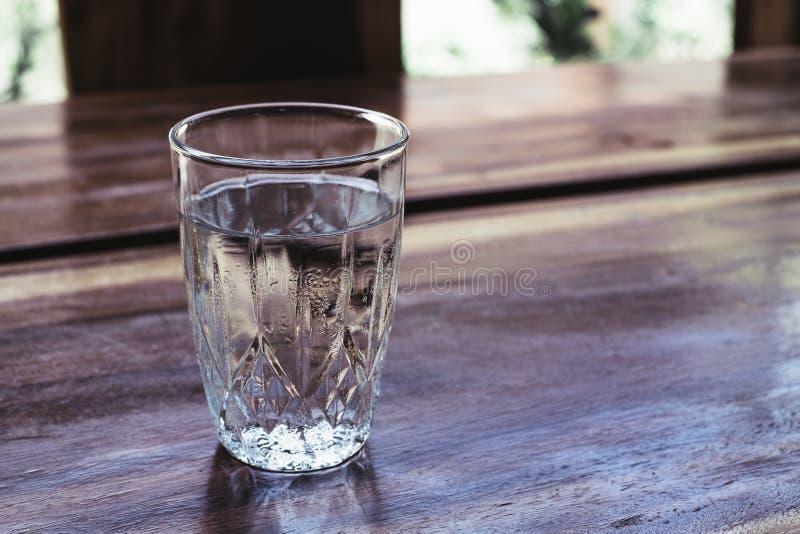 Vidro bebendo limpo completo da água em uma tabela de madeira imagens de stock
