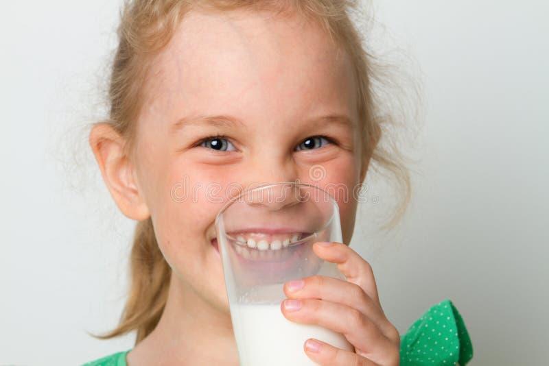 Vidro bonito da terra arrendada da menina do leite imagens de stock