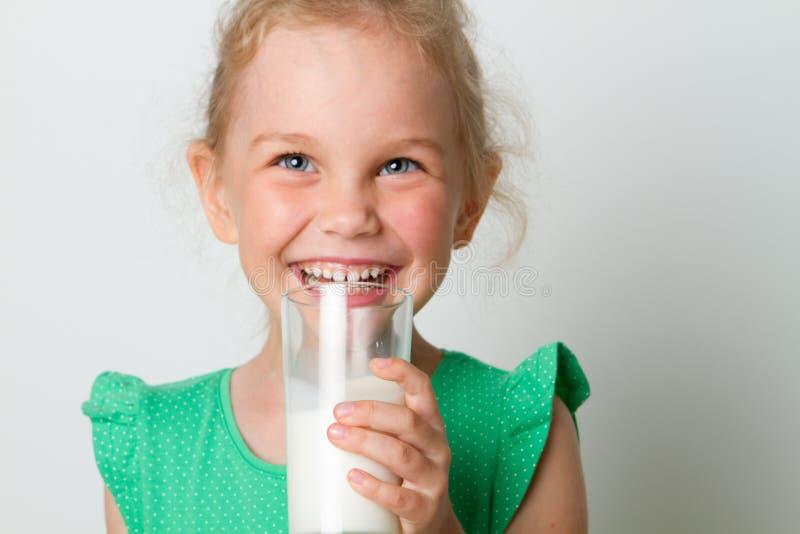Vidro bonito da terra arrendada da menina do leite foto de stock