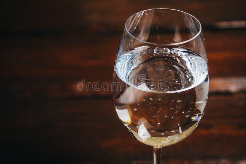 Vidro colhido do vinho branco em um fundo marrom de madeira rústico resto, feriado, partido close up da bebida alcoólica Copie o  imagens de stock royalty free