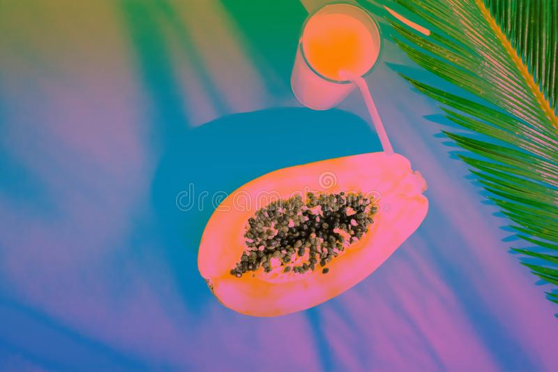 Vidro colocado liso da composição com fruto tropical fresco Juice Halved Papaya Palm Leaf Cerceta e tonificação alaranjada do inc imagem de stock royalty free