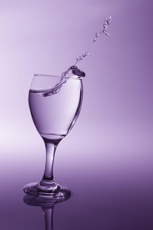 Vidro com água clara que cai sobre ao derramamento com li da parte traseira do roxo foto de stock royalty free