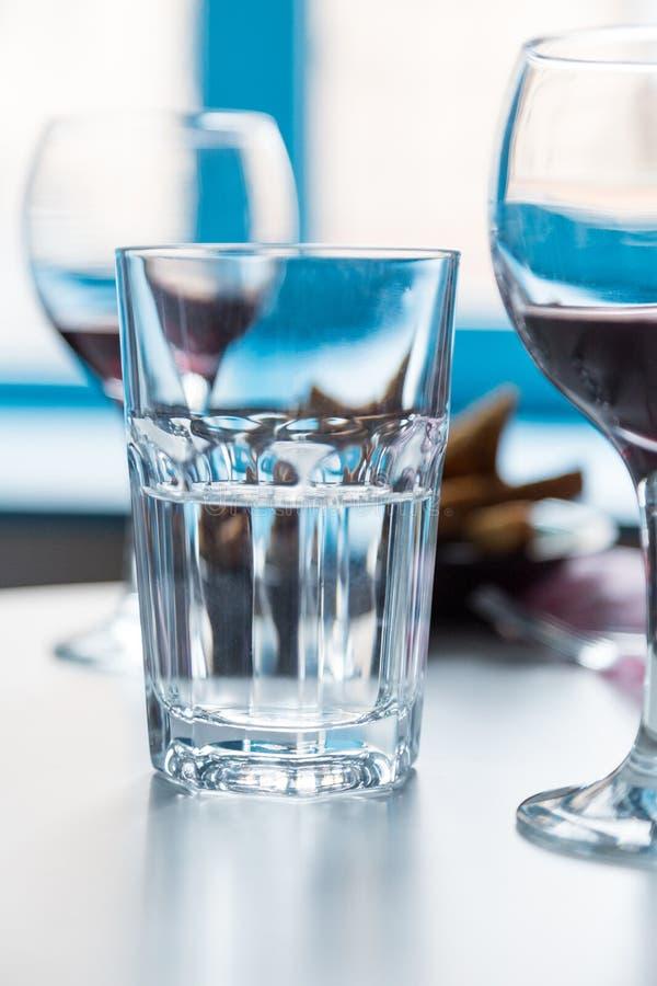 Vidro com água e os copos de vinho no fundo azul da janela fotos de stock