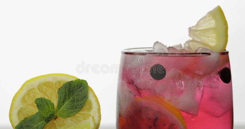 Vidro com bebida vermelha fria com limão, os corintos pretos e os cubos de gelo imagens de stock royalty free