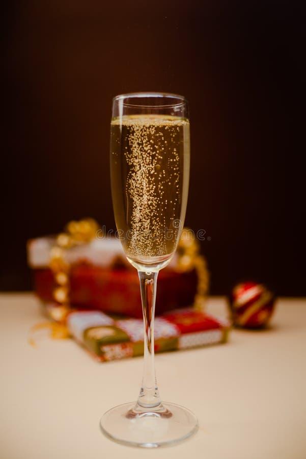 Vidro com bolhas Vidro do shampagne do Natal com presentes no fundo imagem de stock