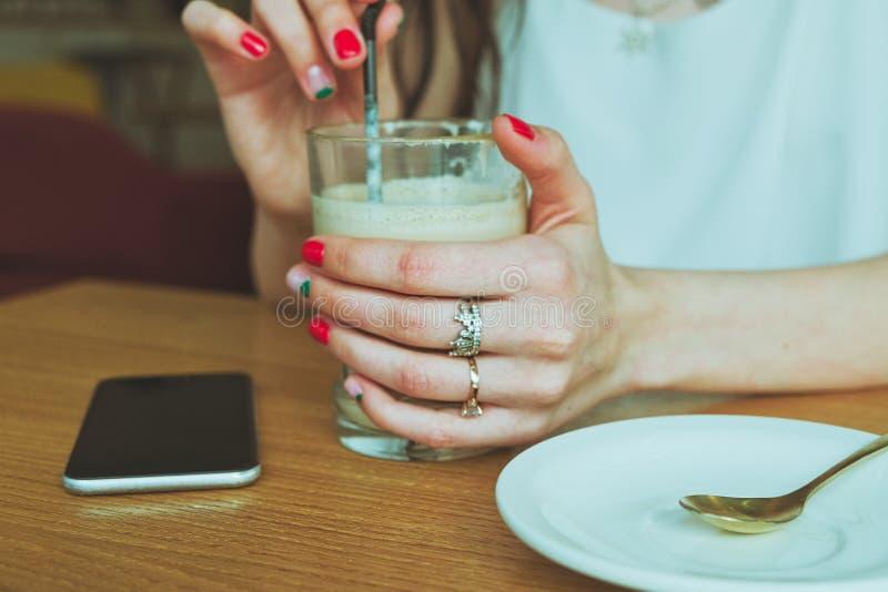 Vidro Com Café Na Mão De Uma Garota Com Smartphone Deitado Na Mesa fotografia de stock royalty free