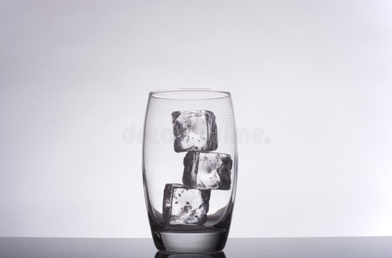 Vidro com cubos de gelo em um fundo do inclinação imagem de stock
