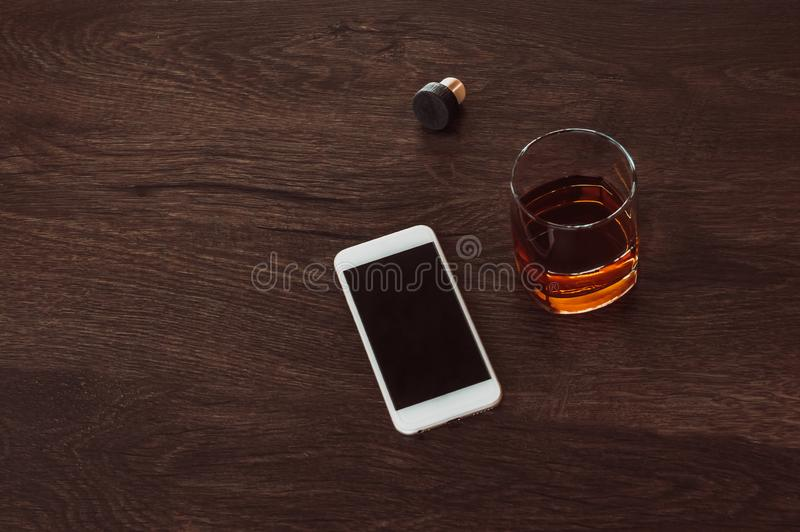 Vidro com mentira do uísque, da cortiça e do telefone celular em uma tabela de madeira imagem de stock royalty free