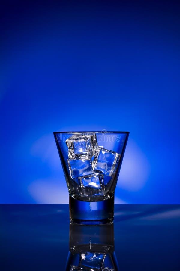 Vidro com os cubos de gelo no fundo azul fotos de stock royalty free