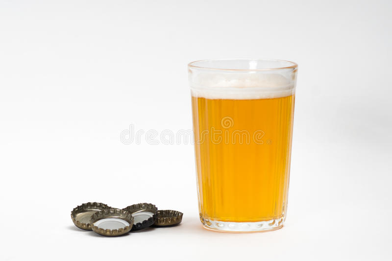 Vidro com os tampões da cerveja e de garrafa imagem de stock