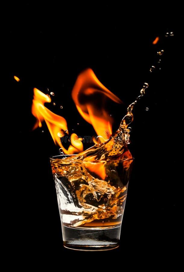 Vidro com respingo e fogo do uísque fotografia de stock royalty free