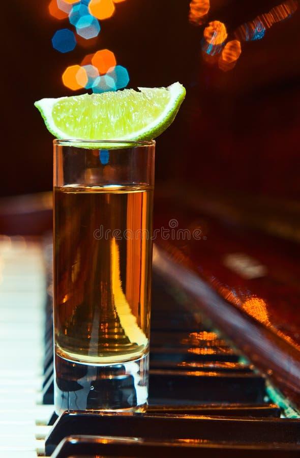 Vidro com tequila em um piano imagem de stock royalty free