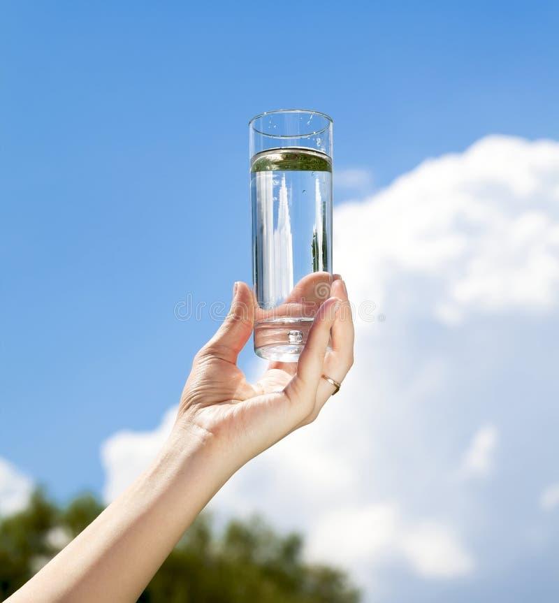 Vidro da água à disposicão imagem de stock