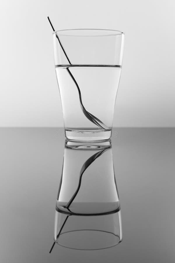 Vidro da água e da colher imagem de stock