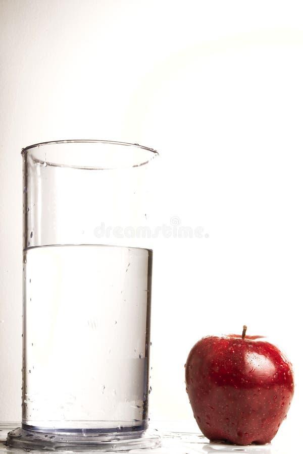Vidro da água e da maçã vermelha imagem de stock