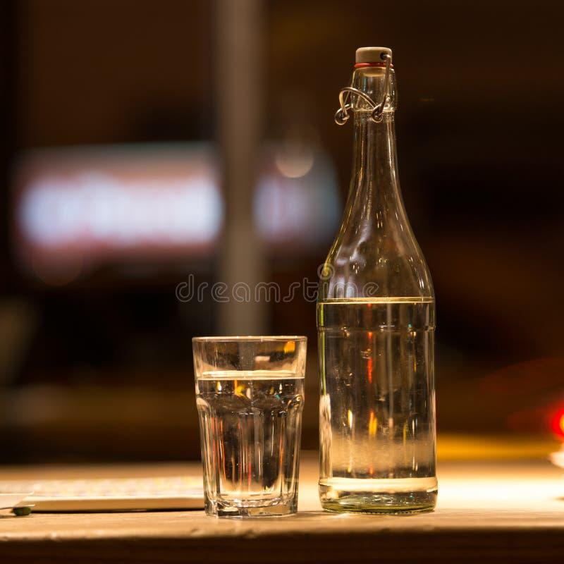 Vidro da água e de uma garrafa na tabela do restaurante fotografia de stock
