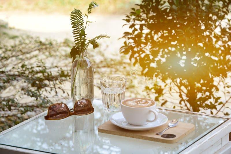 Vidro da água e o café e os óculos de sol na tabela com exterior foto de stock