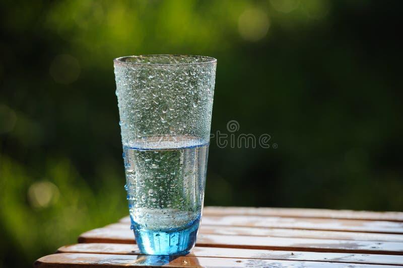 Vidro da água mineral fria na tabela exterior foto de stock