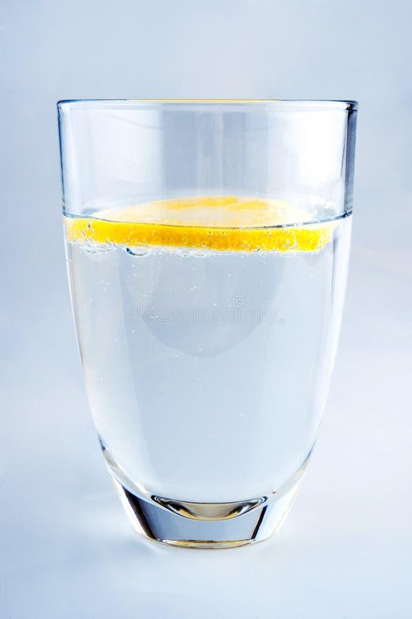 Vidro da água mineral pura com limão imagens de stock