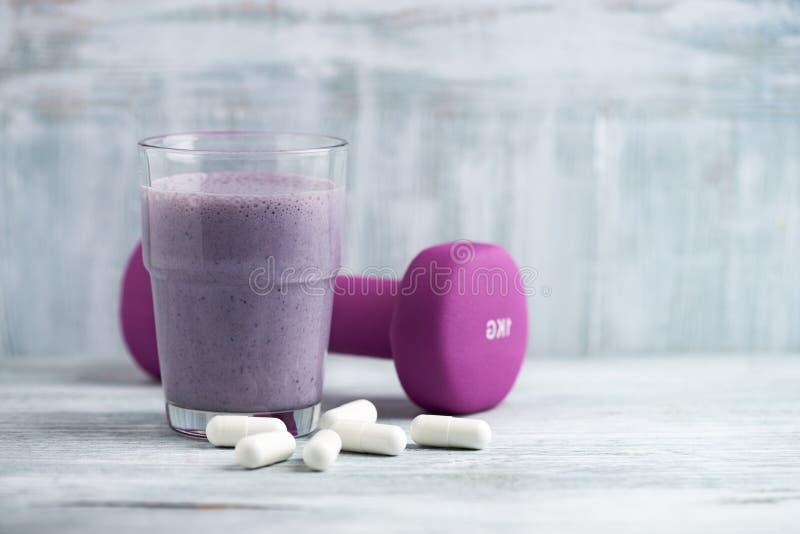 Vidro da agitação da proteína com leite e mirtilos Ácidos aminados de BCAA e um peso violeta no fundo Nutrição do esporte imagem de stock royalty free