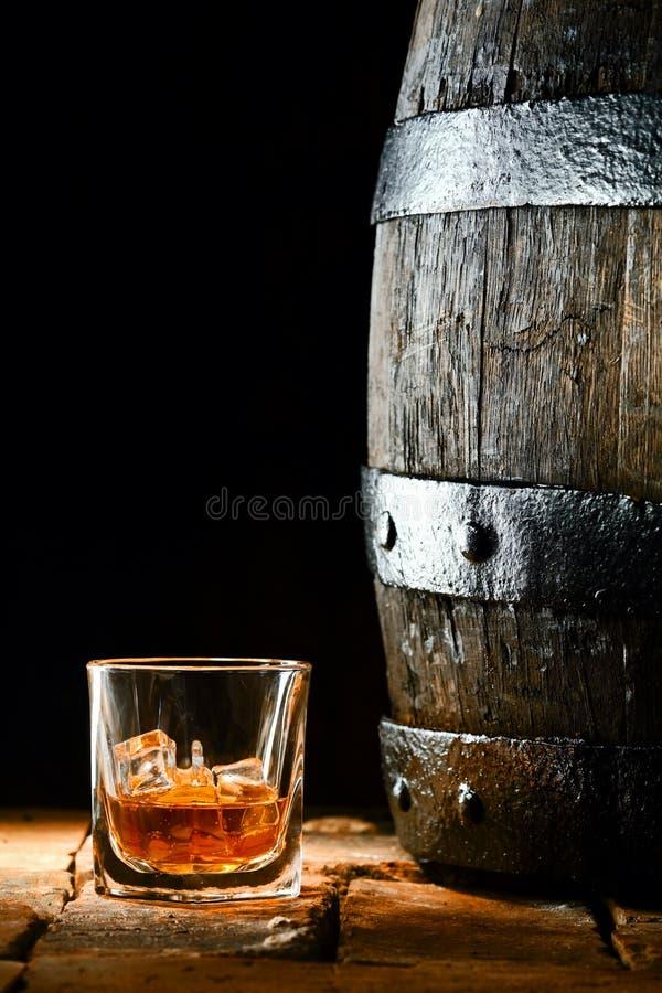 Vidro da aguardente ao lado de um tambor do carvalho fotografia de stock