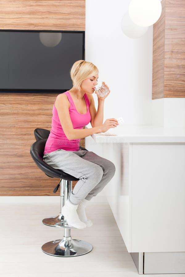 Vidro da bebida da jovem mulher do leite em sua cozinha em imagens de stock