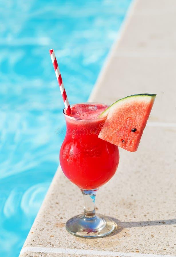 Vidro da bebida do suco do batido e conceito tropical do feriado da piscina imagem de stock
