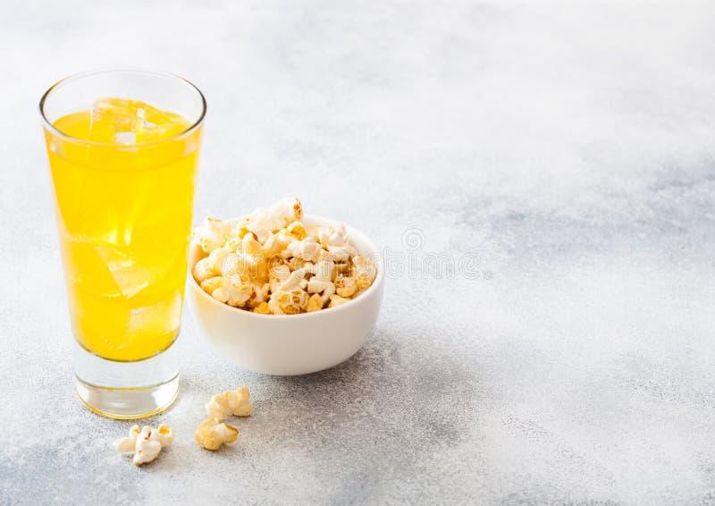 Vidro da bebida da soda alaranjada com cubos de gelo e a bacia branca de petisco da pipoca no fundo de pedra da mesa de cozinha imagem de stock royalty free