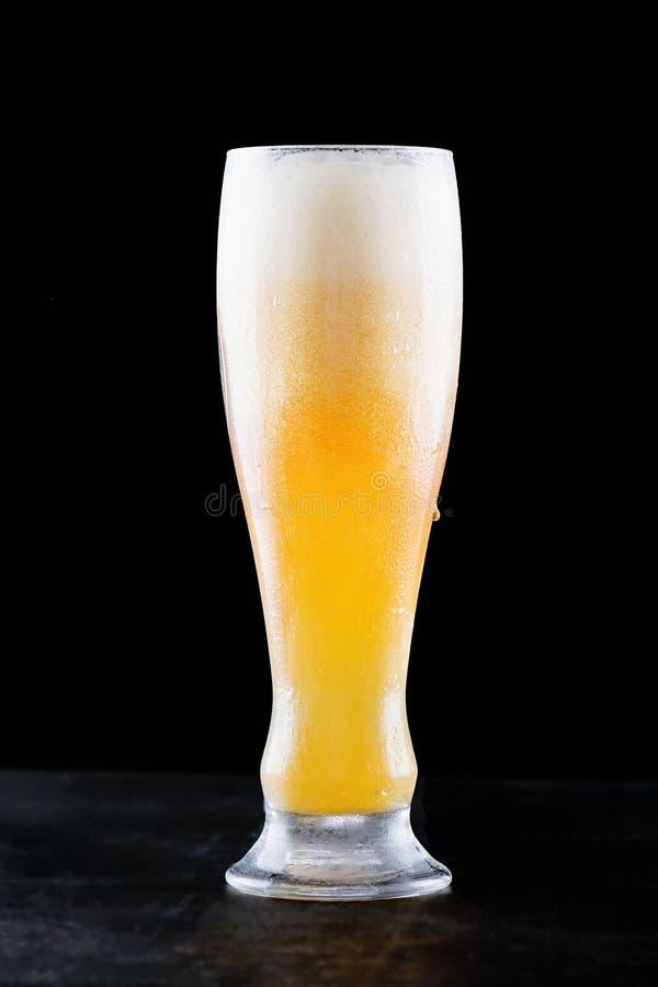 Vidro da cerveja clara fria fresca com a espuma que flui na tabela e da cerveja derramada bonita em um fundo preto imagem de stock