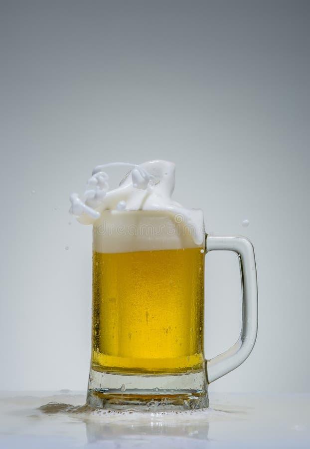 Vidro da cerveja com a espuma que espirra em um fundo cinzento foto de stock