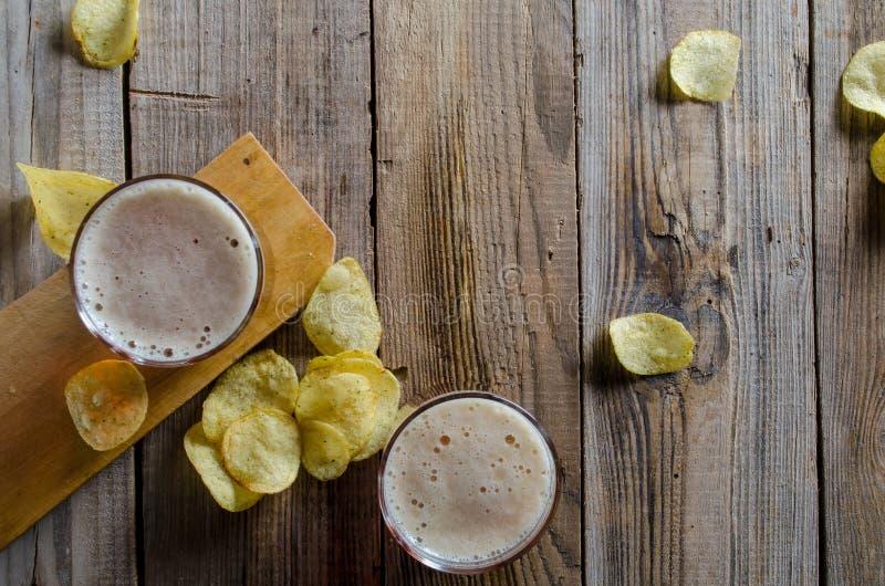 Vidro da cerveja com microplaquetas em um fundo de madeira fotos de stock royalty free