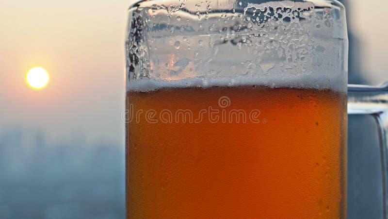 Vidro da cerveja de esboço com o por do sol atrás foto de stock