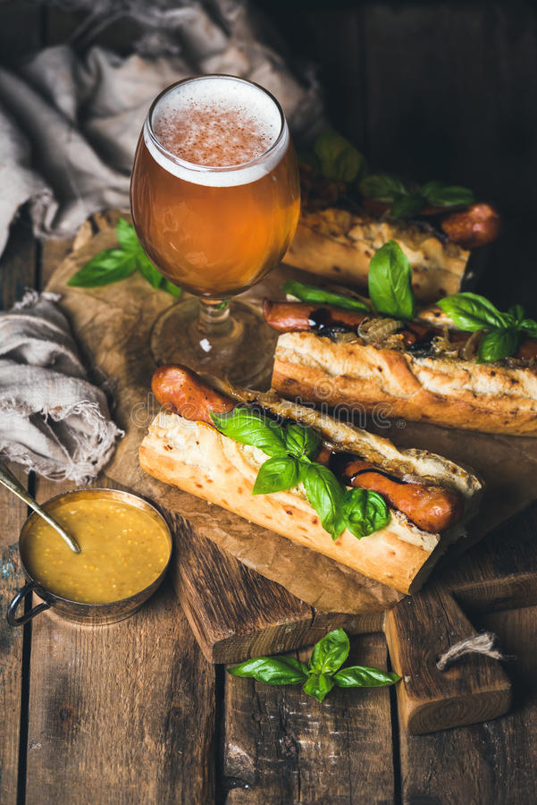 Vidro da cerveja do trigo e de cães de salsicha grelhados no baguette imagens de stock