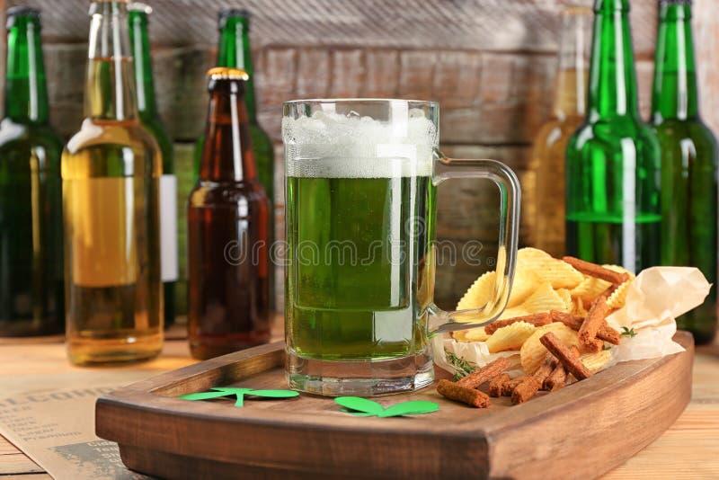 Vidro da cerveja e de petiscos verdes na placa de madeira fotografia de stock royalty free