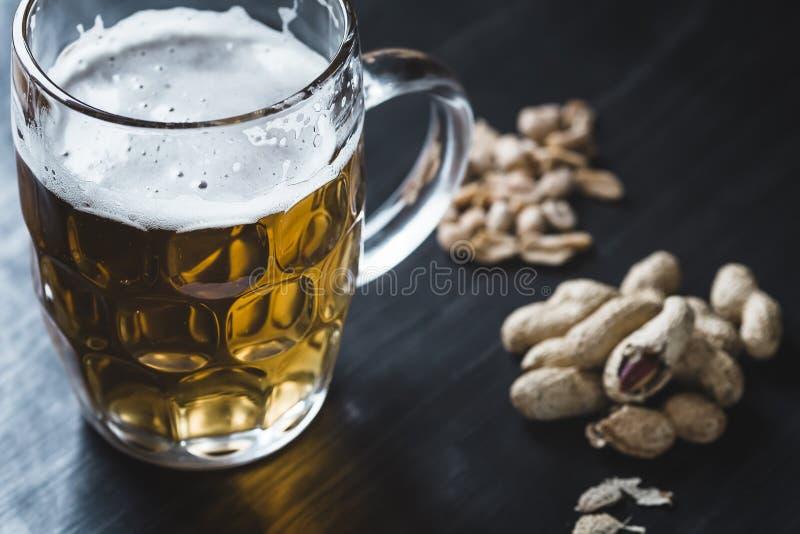 Vidro da cerveja e dos amendoins no fundo de madeira imagem de stock