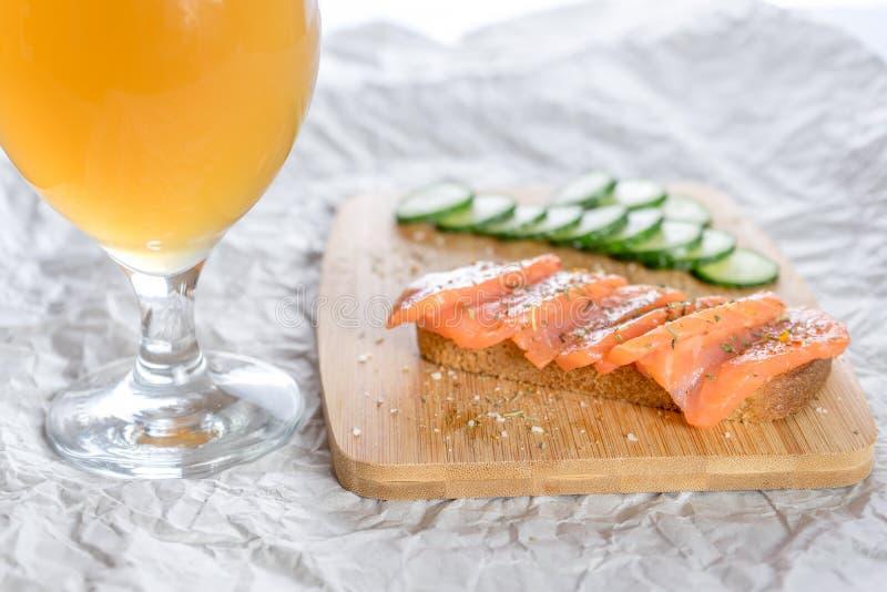 Vidro da cerveja e dos sanduíches com pão, os peixes frescos e os pepinos cortados com as especiarias na bandeja de madeira fotos de stock royalty free