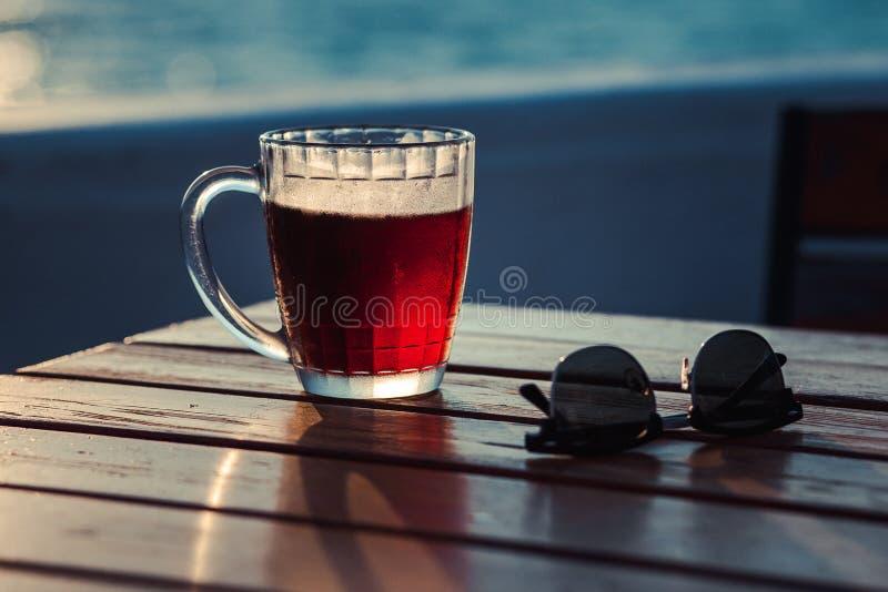 Vidro da cerveja na praia imagens de stock royalty free
