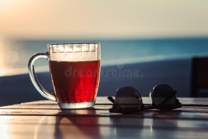 Vidro da cerveja na praia foto de stock