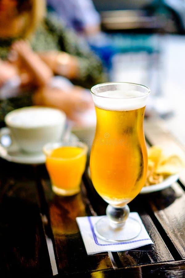 Vidro da cerveja no bar, na mulher e no bebê exteriores no fundo, fotografia de stock