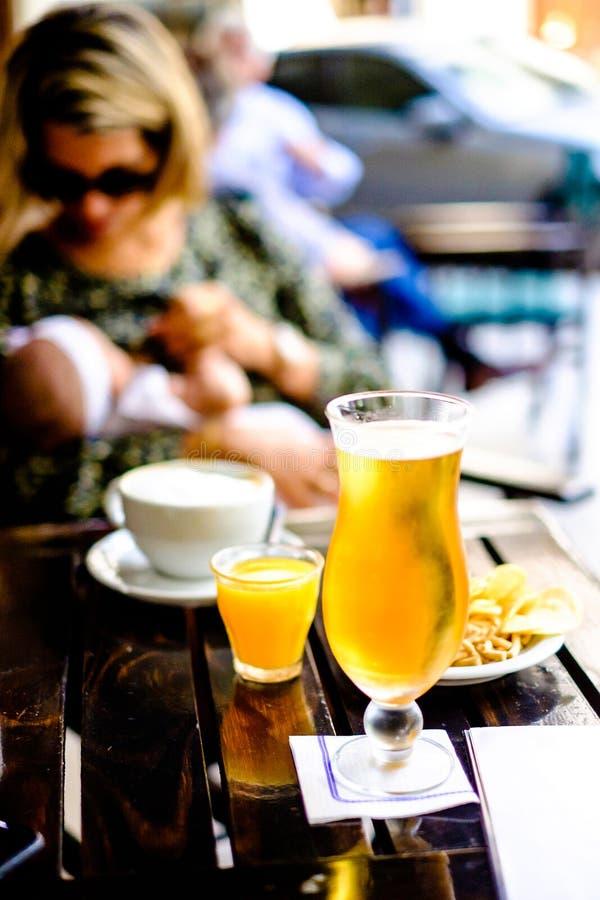 Vidro da cerveja no bar, na mulher e no bebê exteriores no fundo, imagem de stock royalty free