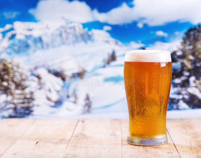 Vidro da cerveja sobre a paisagem do inverno imagens de stock royalty free