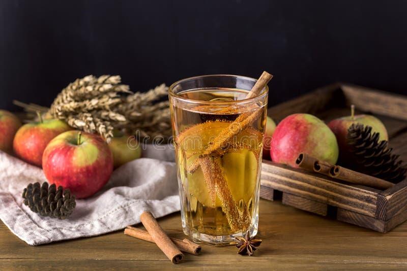 Vidro da cidra saboroso com maçãs e especiarias na bebida de madeira rústica do Natal do fundo imagens de stock royalty free