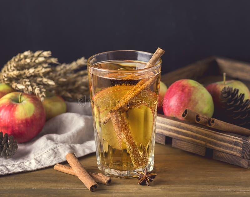 Vidro da cidra saboroso com maçãs e especiarias na bebida de madeira rústica do Natal do fundo tonificada fotos de stock royalty free