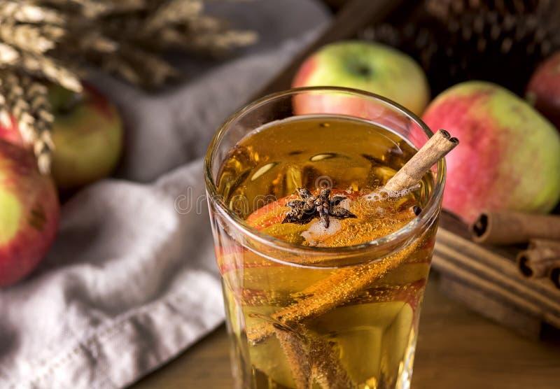 Vidro da cidra saboroso com maçãs e especiarias no fim de madeira rústico da bebida do Natal do fundo acima fotografia de stock royalty free