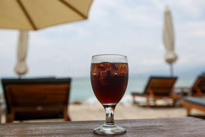 Vidro da cola na praia com guarda-chuvas Bebida refrigerando foto de stock royalty free