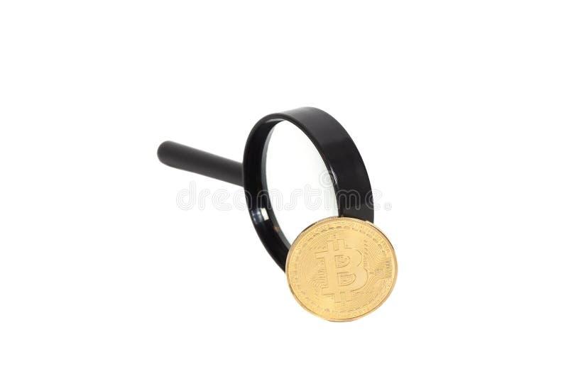 Vidro da lente de aumento com a moeda dourada do bitcoin imagens de stock royalty free