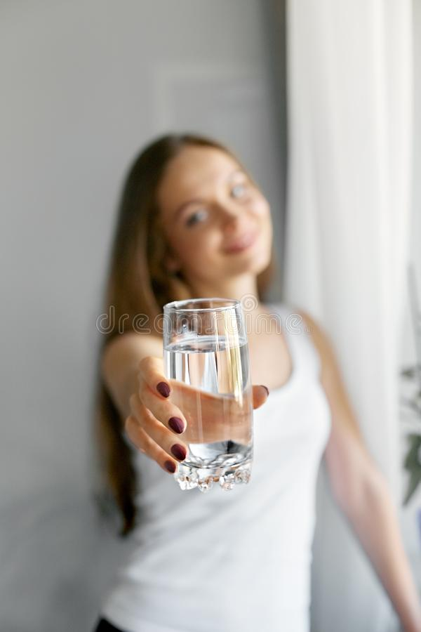 Vidro da mostra da jovem mulher do close up da água Retrato do modelo fêmea de sorriso feliz que guarda o vidro transparente da á imagens de stock