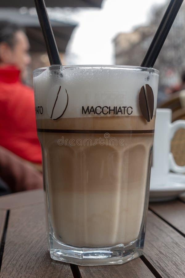 Vidro da posição do macchiato do latte em uma tabela em um café da rua fotos de stock royalty free