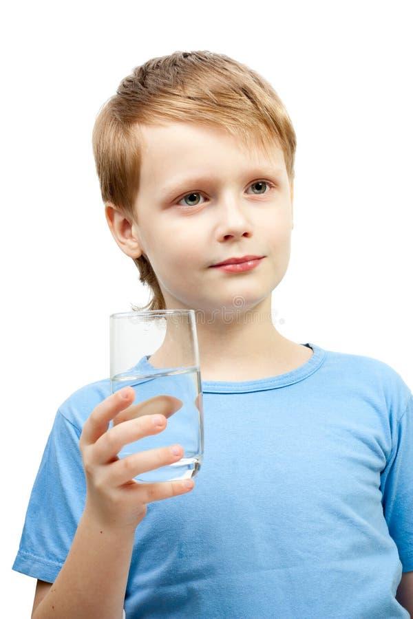 Vidro da preensão do rapaz pequeno da água. fotos de stock