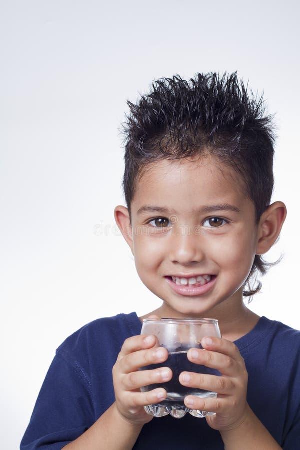 Vidro da preensão do rapaz pequeno da água imagens de stock